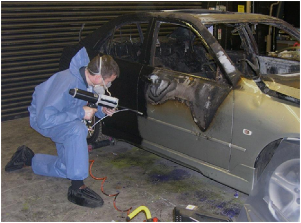 Dirt and soot being removed from the surface of a burnt out car as part of the SFU examination